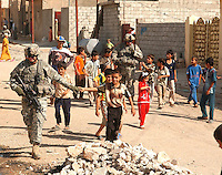 U.S. Army Staff Sgt. Shawn Smith takes the hand of an Iraqi boy during a visit to a local street market in Kirkuk, Iraq, Sept. 25, 2006.  Smith is assigned to the 2nd Battalion, 35th Infantry Regiment, 25th Infantry Division. (U.S. Air Force photo by Master Sgt. Steve Cline) (Released)