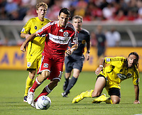 Chicago Fire midfielder Marco Pappa (16) dribbles away from Columbus Crew midfielder Brian Carroll (16, behind) and defender Gino Padula (4, right).  The Chicago Fire tied the Columbus Crew 0-0 at Toyota Park in Bridgeview, IL on July 11, 2009.