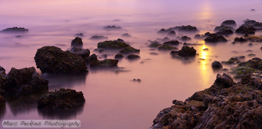 Taken at Little Corona Beach in Corona Del Mar (Newport Beach), CA, here we see light reflecting off of the silky smooth water among the rocks at the beach.  Thanks to the long exposure, it looks like there's mist creeping in.