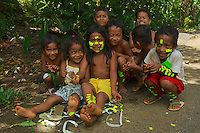 Happy Young Pohnpei girl having fun wioth yellow price tags from the supermarket on the island of Pohnpei, Micronesia