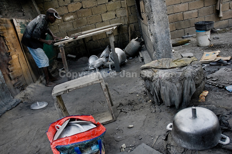 A Haitian man polishing an aluminium pot in the aluminium recycling shop on the street of Port-au-Prince, Haiti, 11 July 2008.