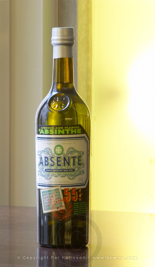 Bottle of Absente a brand of Absinthe Pastis is a spirit high alcohol drink flavoured flavored with herbs such as anise (badiane, anis étoilé etoile) and other spices. It is sometimes called pastis or Absinth absinthe. It is served in a tall glass with ice and you pour water on it. It gets cloudy milky when water is added. It is a favourite drink aperitif in Provence Southern France.