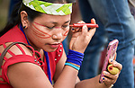 A woman paints her face with urucum before a march by indigenous people through the streets of Atalaia do Norte in Brazil's Amazon region on March 27, 2019. They were protesting a central government plan to turn control of health care over to municipalities, in effect destroying a federal program of indigenous health care. Indian rights activists are worried that the government of President Jair Bolsonaro is reducing or eliminating protections for the country's indigenous people.