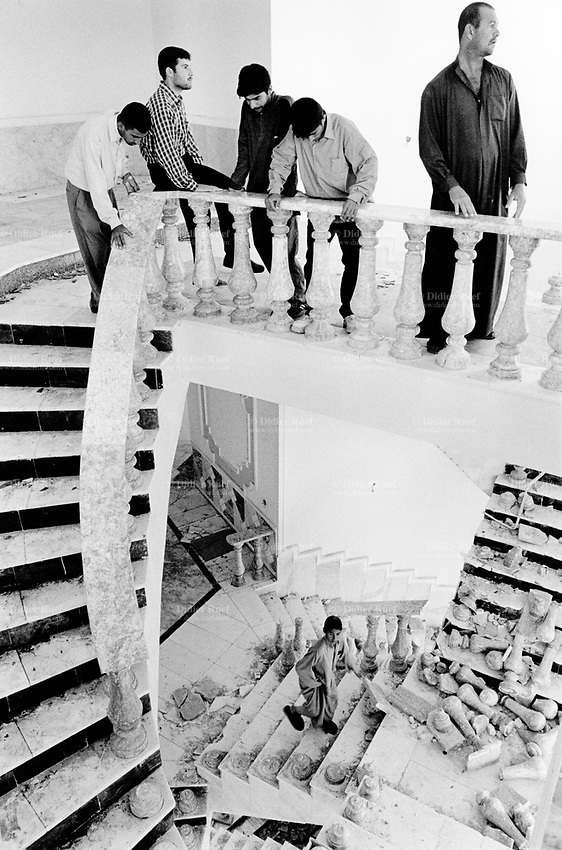 Iraq. Tikrit. Looters in the Saddam Hussein's palace on the Tigrus river. Broken columns made of marble from Carrara in Italy are laying on the staircase. © 2003 Didier Ruef