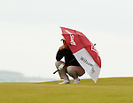 Padraig Harrington shelters from a squally shower on the q8th fairway during the Barclays Scottish Open, played over the links at Castle Stuart, Inverness, Scotland from 7th to 10th July 2011:  Picture Stuart Adams /www.golffile.ie  7th July 2011