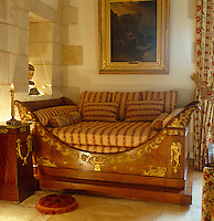An Empire daybed with a matching sidetable in a corner of the drawing room is decorated with gilt ormolu