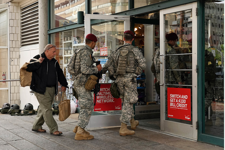 A man follows heavily armed National Guard troopers on patrol into a shop in Baltimores' inner harbor, April 30, 2015. to go with Nick O'Malley story.  photo by Trevor Collens