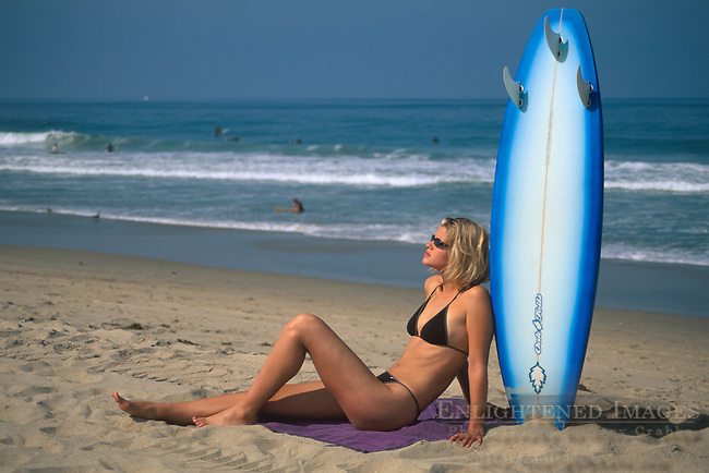 Beautiful young woman in bikini resting against surfboard in sand, Manhattan Beach, Los Angeles County, California