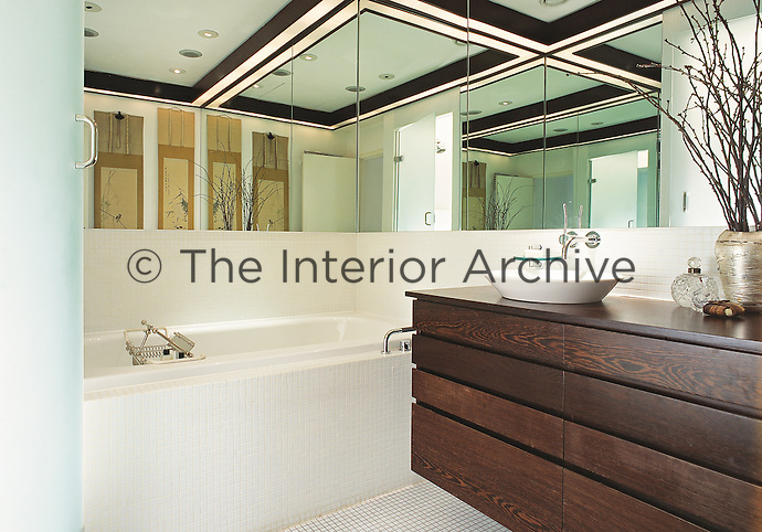 A contemporary modern tiled bathroom. A washbasin is set on a wooden drawer unit next to a bath. Mirrors on the walls creates a sense of space in the room.