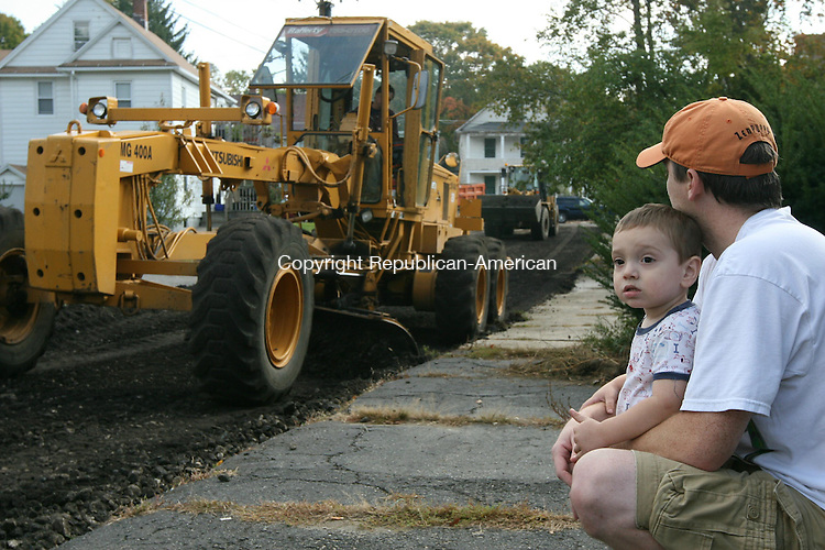 TORRINGTON, CT - 9 October, 2008 - 100908MO01 - Jacob Cornett, 22 months, and Chad Cornett watch Kurt Rafferty, president of Rafferty Fine Grading, Inc., re-grade Jardon Street Thursday as Torrington began a two-week effort to re-grade and re-pave local roads including Bannon Street, Farmstead Lane, Goodwin Street, Jardon Street, Monroe Street, Nutmeg Drive and Sunset Lane. Chad Cornett said Jacob was an enthusastic spectator, rising around 6 a.m. when equipment began to arrive. As of 11 a.m., Jacob had not yet tired of the spectacle. City officials said vehicles parked on those streets between 7 a.m. and 5 p.m. during construction are subject to being towed away at their owner's expense. Jim Moore Republican-American.