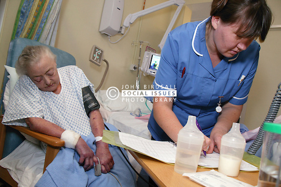 Staff nurse assessing elderly patient on general medical ward,