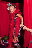 Girl in red feather boa standing in photo booth.
