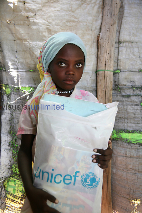 Young girl carrying a UNICEF bag of supplies in Sudanese refugee camp, Chad