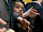 "(Boston MA 01/14/18) Nathaniel Jukanovich, 8, of Wentham, holds the hands of his adopted parents parents, Dano and Jennifer Jukanovich,  as ""We Shell Over Come"" is sung in the church, during the annual Martin Luther King Jr. Convocation at the Twelfth Baptist Church in Roxbury, Sunday, January 14, 2018, in Boston. (Herald Photo by Jim Michaud"