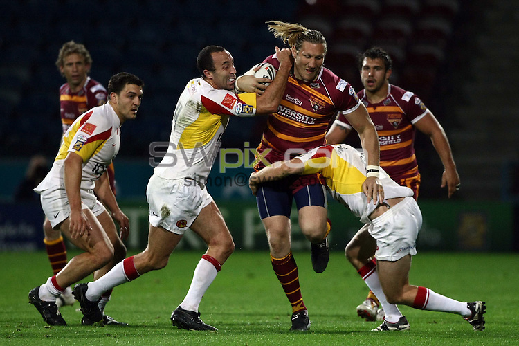 PICTURE BY VAUGHN RIDLEY/SWPIX.COM - Rugby League - Super League Playoffs - Huddersfield v Catalans - Galpharm Stadium, Huddersfield, England  - 25/09/09...Copyright - Simon Wilkinson - 07811267706...Huddersfield's Eorl Crabtree is tackled by Catalans Adam Mogg and Casey McGuire.