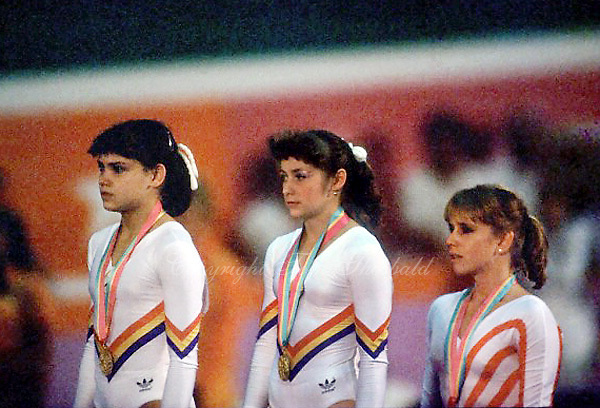 August 6, 1984; Los Angeles, California, USA;  (L-R) Artistic gymnastics stars Simona Pauca and Ecaterina Szabo of Romania share gold medal win with Kathy Johnson of USA taking bronze in the balance beam event final at 1984 Los Angeles Olympics. Copyright 1984 Tom Theobald
