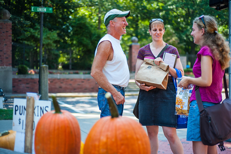 Jeff Latta talks to Saryn Cranston, a third year graduate student, and Emily Price, a doctoral student, about pumpkins at the OU Mini Farmer's Market on Friday, September 7, 2012 at Howard Park.