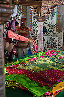 Fatehpur Sikri, Uttar Pradesh, India.  Inside the Mausoleum of Sheikh Salim Chishti.  Woman Tossing Rose Petals on the Grave.   Prayers are often offered in hopes of conceiving a child.