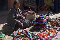 A woman selling fabrics and tomatoes in Chichicastenango Market, Guatemala.