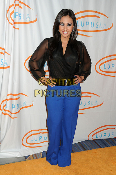 Francia Raisa.12th Annual Lupus LA Orange Ball held at the Beverly Wilshire Hotel, Beverly Hills, California, USA..May 24th, 2012.full length trousers blue black blouse sheer hands on hips.CAP/ADM/BP.©Byron Purvis/AdMedia/Capital Pictures.