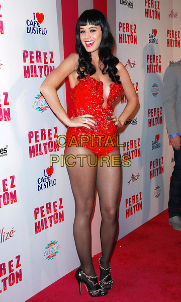 KATY PERRY .Attending Perez Hilton's Carn-Evil 32nd Birthday Party held at Paramount Studios, Los Angeles, California, USA, 27th March 2010..arrivals full length black red cleavage cut out low bodice leotard body tights gold military costume epaulettes  jewel encrusted shoes booties ankle boots open toe hands on hips smiling sparkly sequined sequin beaded .CAP/ADM/TC.©T.Conrad/Admedia/Capital Pictures