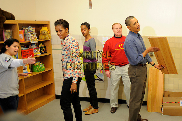 United States President Barack Obama (R) inspects a shelf as he and first lady Michelle Obama (2nd,L) and daughter Malia (C) join volunteers in a library as they participate in a service project, at Browne Education Center, in Washington, DC, USA, on the Martin Luther King Jr national holiday, 16 January 2012. The project was in memory of the legacy of community service, promoted by the late civil rights leader, who was assassinated in 1968.  .CAP/ADM/MT.©Mike Theiler/Pool/CNP/AdMedia/Capital Pictures.