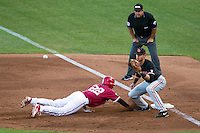 Oregon State first baseman Danny Hayes (9) catches a pickoff throw as Indiana Hoosiers baserunner Indiana Hoosiers Justin Cureton (22) dives back during Game 9 of the 2013 Men's College World Series  on June 19, 2013 at TD Ameritrade Park in Omaha, Nebraska. The Beavers defeated the Hoosiers 1-0, eliminating Indiana from the tournament. (Andrew Woolley/Four Seam Images)