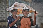 Two boys walk under one flimsy umbrella in Tuingo, an ethnic Chin village in Myanmar.