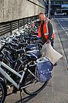 Nederland, Utrecht, 11-04-2011 Fietsen. Schoonmaker op Jaarbeursplein ruimt de rommel op tussen de fietsen in de fietsrekken. Foto: Gerard Til/Hollandse Hoogte