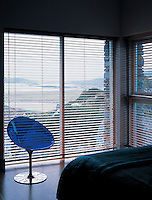 A Philippe Starck blue Kartell Eros chair stands in front of a window with venetian blinds in a modern bedroom.