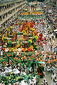 Rio de Janeiro, Brazil. Carnival; overview of sambadrome with colourful floats and people; Bahianas and palm trees.