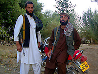 A sub-commander and foot sioldier from the Wardak Mobile Patrol Unit with a chinese motorcycle before they go out on patrol armed with an AK47 machine gun