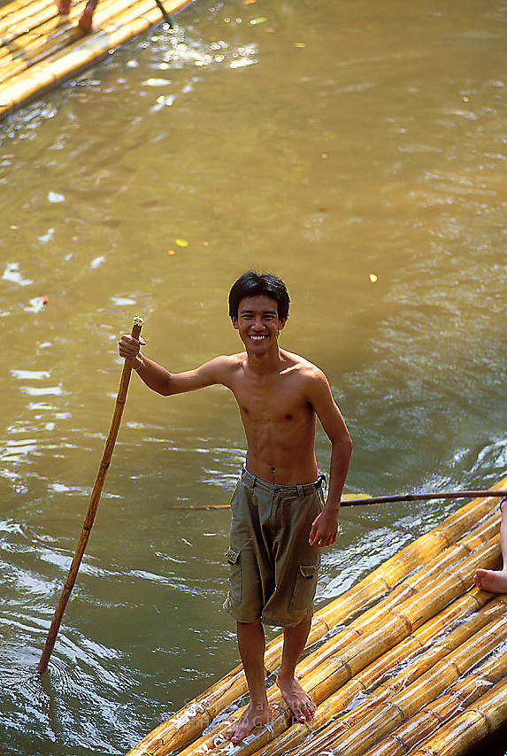 Young male bamboo raft driver smiling at camera, Chiang Mai, Thailand
