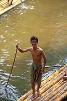 Young male bamboo raft driver smiling at camera, Chiang Mai, Thailand