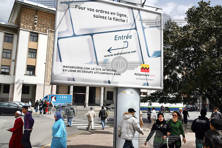 Pedestrians walk beneath an advertisment for an internet bank account of the Attijariwafa bank. This is the second largest bank in Morocco.
