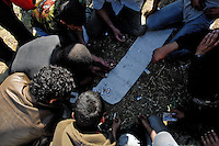 Haraga immigrants play cards and waiting for the night to enter illegaly to the port of Tanger, Morocco, 21 January 2007. Every day tens of Moroccan young men try to cross ilegally the Strait of Gibraltar. ?Harraga? (immigrants in Arabic) come to Tanger from all over Morocco. They try their good luck and hidden between the wheels of a truck they attempt to board on a ferry and get to Spain, eventually further to Europe. Considering the thorough checks at the port only few of them make it. Therefore they spend months living on a beach, in huts along the walls of the port, begging for food and waiting for the right night so as their dream about Europe came true.