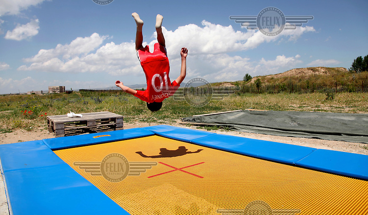 A child does a somersault on a trampoline at Armenian Caritas, 'Emil's Aregak', a supportive and developmental day care centre for children with disabilities and disadvantaged children.