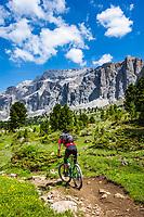 Italy, South Tyrol (Trentino - Alto Adige), Dolomites, near Selva di Val Gardena: Mountainbiker with Sella Group at Sella Pass Road | Italien, Suedtirol (Trentino - Alto Adige), oberhalb von Wolkenstein in Groeden: Mountainbiker vor der Sellagruppe an der Sella-Joch-Passstrasse