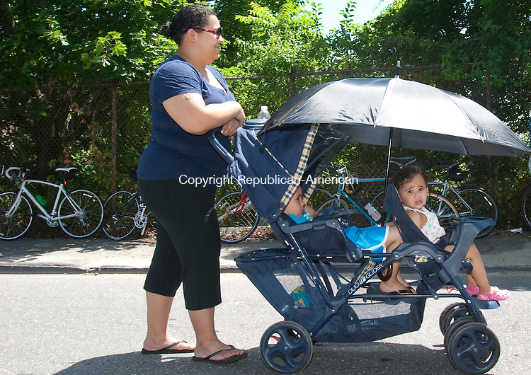WATERBURY, CT. 29 June 2010-062910SV01--Victoria Encarnacion walks with her two children Micaela Jimenez, 1, and Josiah Jimenez, 4, on Jewelry Street in Waterbury Tuesday. The kids were trying to stay cool under the umbrella as the temperatures rose above 90 degrees.<br /> Steven Valenti Republican-American