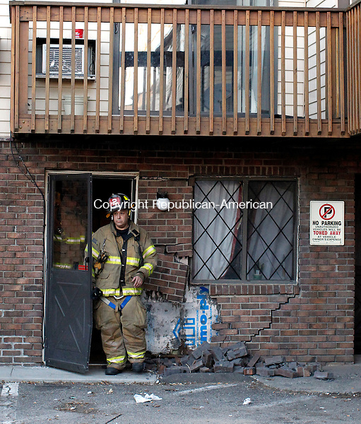 Waterbury, CT-26 February 2012-022612CM13- A firefighter leaves an apartment after a vehicle backed into the building, causing damage  to the structure Sunday afternoon in Waterbury.  Christopher Massa Republican-American
