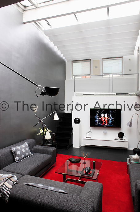 In the living room an entire wall has been painted in silver metalic paint and the fixtures and fittings combine to create an urban high-tech look