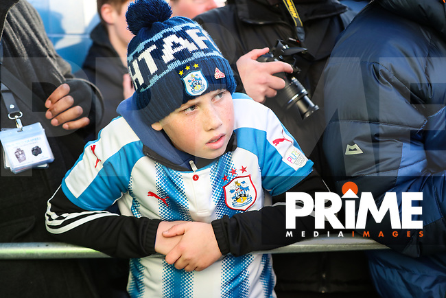 A young Huddersfield Town fan watches players from both teams get off the team coaches before the FA Cup 5th round match between Huddersfield Town and Manchester United at the John Smith's Stadium, Huddersfield, England on 17 February 2018. Photo by Thomas Gadd / PRiME Media Images.