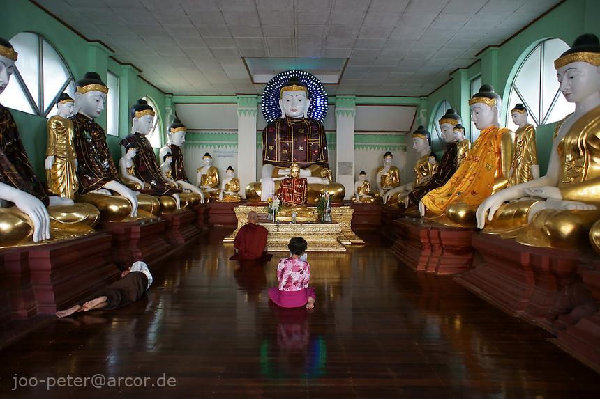 worshipper praying in buddha temple on Shwedagon pagoda complex, Yangon, Myanmar, 2011