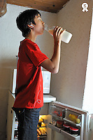 Teenage boy with mp3 player drinking milk (Licence this image exclusively with Getty: http://www.gettyimages.com/detail/91276465 )