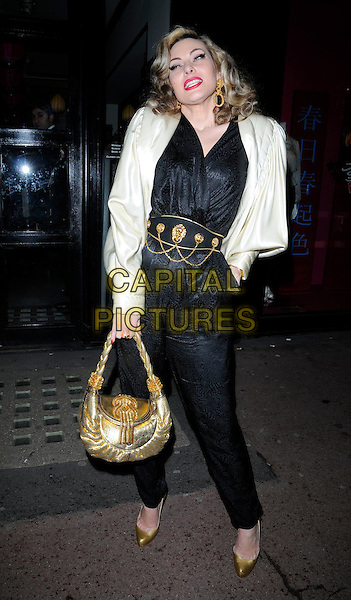 IMMODESTY BLAIZE.The Shanghai Tang Chinese New Year Party, Shanghai Tang boutique, London, England..February 9th, 2010.full length black catsuit jumpsuit gold belt chains bag purse shoes white silk satin jacket shoulder pads hand in pocket.CAP/CAN.©Can Nguyen/Capital Pictures.