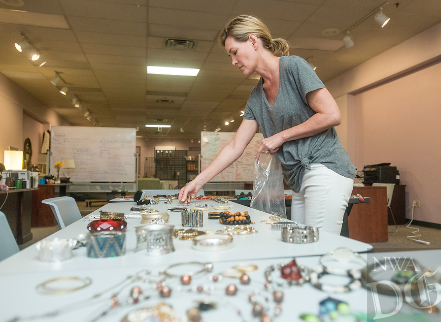 NWA Democrat-Gazette/BEN GOFF @NWABENGOFF<br /> Kate Butler of Bentonville sorts jewelry while volunteering Saturday, Aug. 4, 2018, during a 'Suit Sorting Saturday' at Dress for Success Northwest Arkansas in Frisco Station Mall in Rogers. Dress for Success, with an additional boutique in Springdale, helps empower women entering the workforce by providing support, classes and appropriate professional attire free of charge. Their clients are referred to them from other area organizations, and include women trying to overcome poverty, new citizens and those returning to society after being incarcerated. Volunteers gather once a month at the Rogers location for a Suit Sorting Saturday to help with intake, sorting, cleaning and repair of donated clothing. The organization plans to hold their annual inventory reduction sale Aug. 25., which is open to the general public and helps fund the organization.