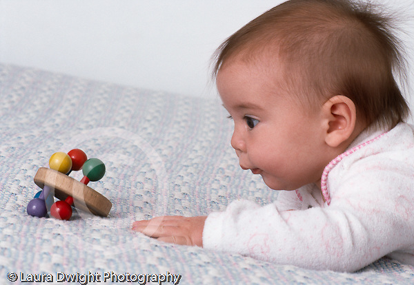 4 month old baby girl on stomach very interested in toy reaching horizontal