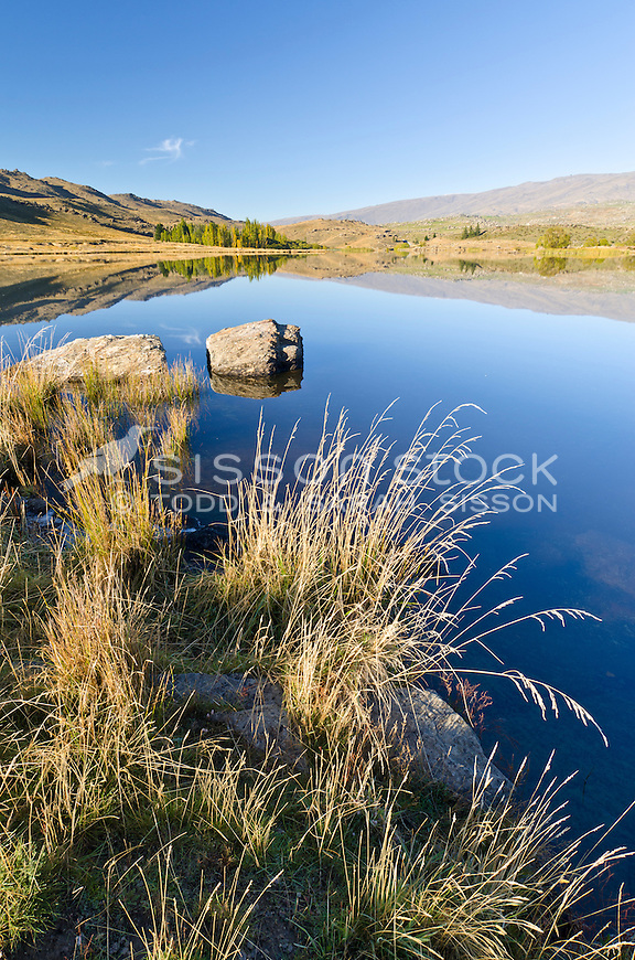 A calm and tranquil reflection in the early morning at Butchers Dam near Alexandra, Central Otago, South Island, New Zealand.