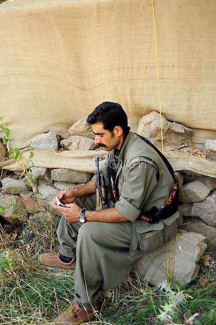 QANDIL, IRAQ: A guerrilla with the Kurdistan Worker's Party (PKK) reviews photos he took of PKK guerrillas killed in an attack by the Turkish military along the border between Iraq and Turkey..The Kurdistan Workers' Party (PKK) is a Kurdish organization fighting for Kurdish autonomy in Turkey.  It is deemed a terrorist group by the USA and the EU. The organization's guerillas are based in the Qandil mountains that make up the border between Iraq and Turkey..Photo by Hawre Majid/ Metrography