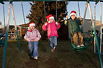 3 kids playing outside dressed in Christmas Hats